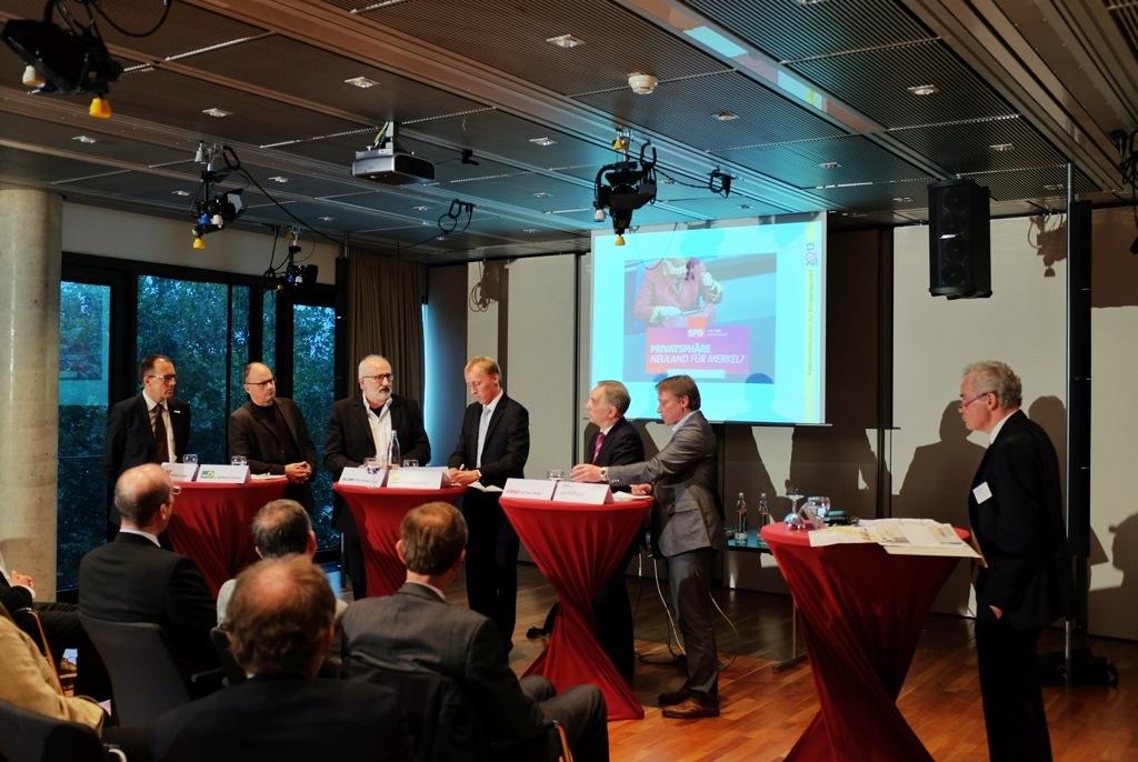 Hans-Christoph Seewald (rechts) leitet eine Podiumsdiskussion mit Parteivertretern.